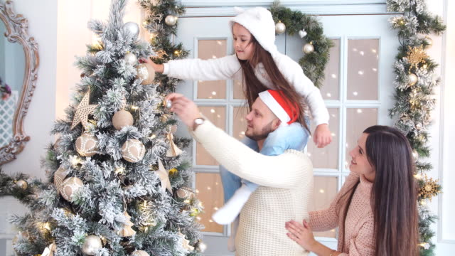 Parents and young girl having fun together near Christmas tree video
