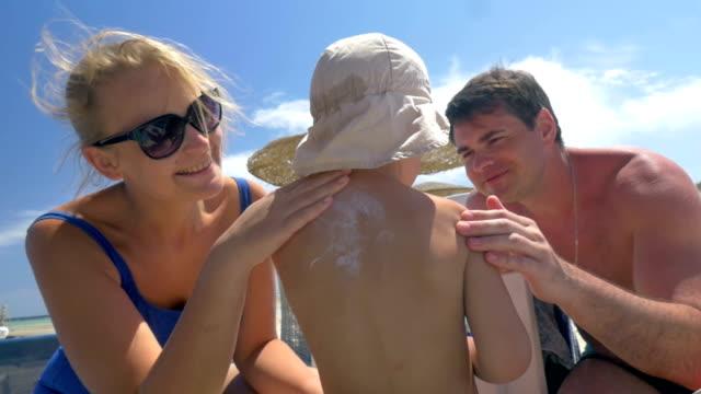 vídeos de stock e filmes b-roll de pais aplicar protetor solar na childs pele - protetor solar