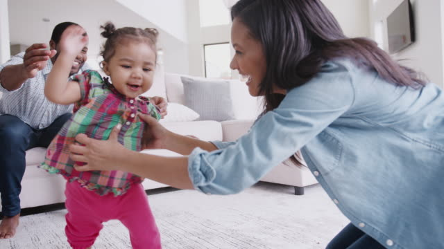 Parents At Home Encouraging Baby Daughter To Take First Steps