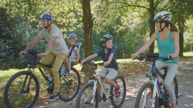 TS Parents cycling in the sunny park with one son riding his bike and the other sitting in the seat on his dad's bike