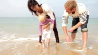istock Parents Dipping Daughters Toes Into Sea 164265157