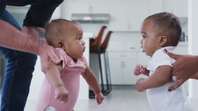 Parents Encouraging Baby Son And Daughter To Interact With Each Other