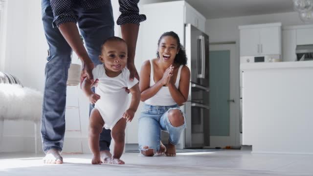 föräldrar uppmuntra leende baby son att ta första stegen och gå hemma - bebis bildbanksvideor och videomaterial från bakom kulisserna