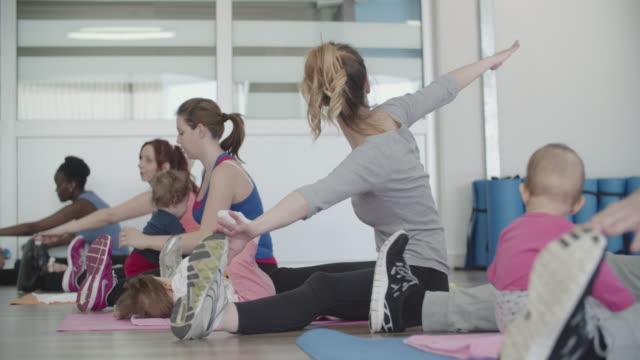 4 k : eltern mit ihren babys training in einem fitness-studio. - fitnesskurs stock-videos und b-roll-filmmaterial