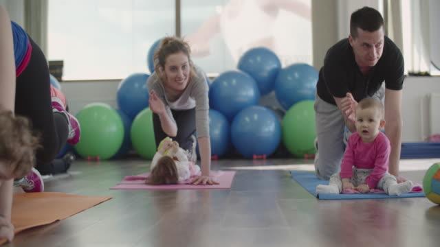 4 k : training mit ihren eltern, babys. - fitnesskurs stock-videos und b-roll-filmmaterial