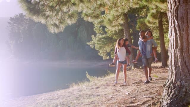 親が子供を与える乗り物をピギーバックは、湖で歩きながら ビデオ