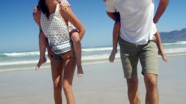 おんぶをビーチで彼らの子供に与える親 ビデオ