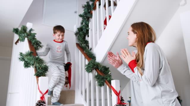 stockvideo's en b-roll-footage met ouders groet opgewonden kinderen dragen van pyjama's trap holding kousen op kerstochtend rennen - christmas tree