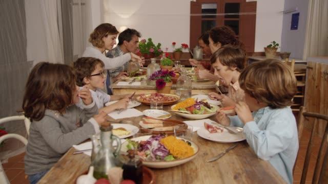 vidéos et rushes de parents ayant des aliments ayant des enfants à table à manger - diner entre amis