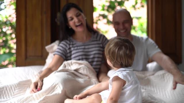 föräldrar att ha kul med en söt dotter på sängen - 35 39 år bildbanksvideor och videomaterial från bakom kulisserna