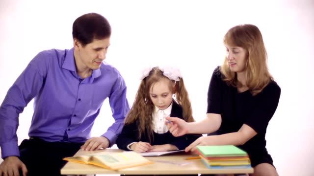 i genitori aiutano la figlia a fare i compiti - nastro per capelli video stock e b–roll