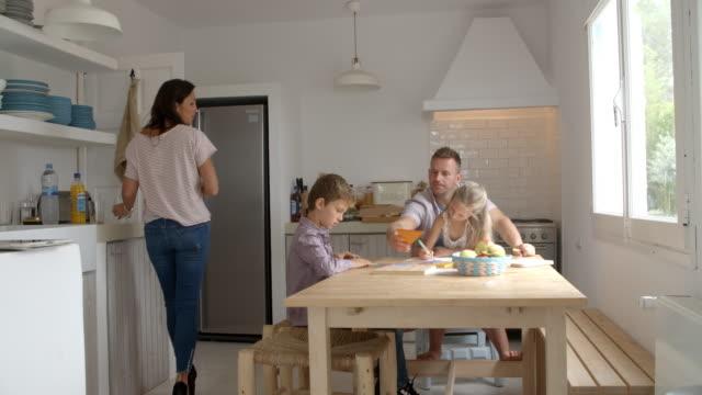 Parents aidant les enfants avec des devoirs à la table de cuisine - Vidéo