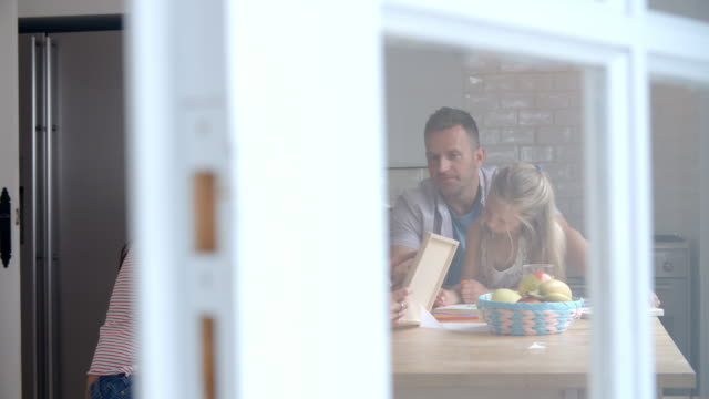 Parents Helping Children With Homework At Kitchen Table video