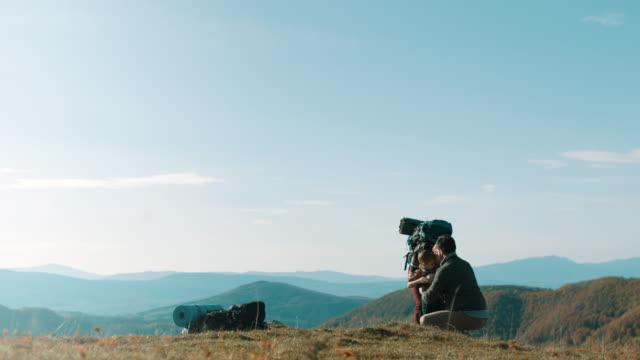 vidéos et rushes de parents en serrant les fils sur le dessus de la montagne - femme seule s'enlacer