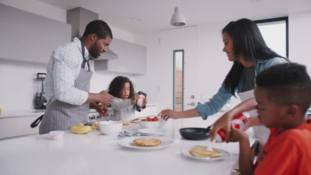 parents in kitchen with children making pancakes together - pancake video stock e b–roll