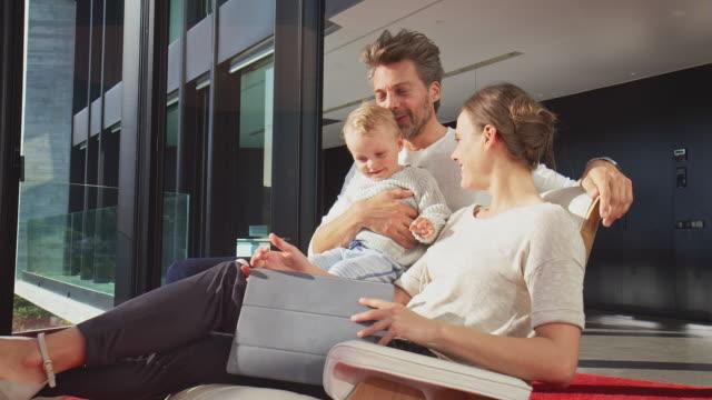 vidéos et rushes de parents en regardant les fils à l'aide de tablette numérique - luxe