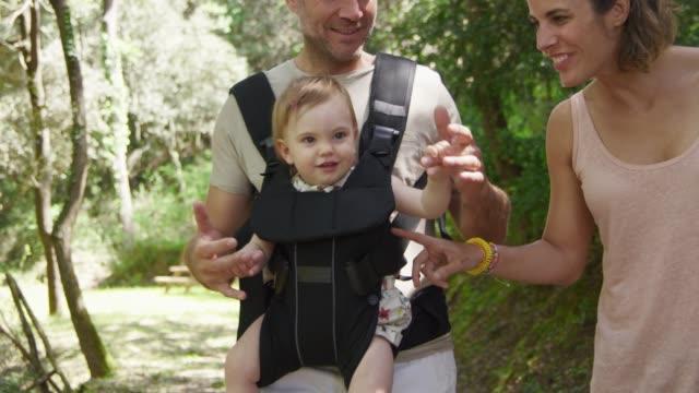 föräldrar leker med barnet medan promenader i skogen - enbarnsfamilj bildbanksvideor och videomaterial från bakom kulisserna