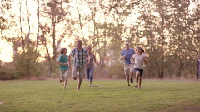 Parents running after kids in a park playing video
