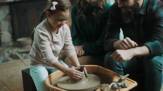 Parents suporting daughter to learn how to make pottery video