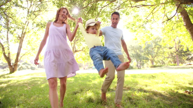 Parents swinging a little toddler girl towards the camera Happy parents swinging a cute little toddler girl towards the camera while walking, slow motion swinging stock videos & royalty-free footage