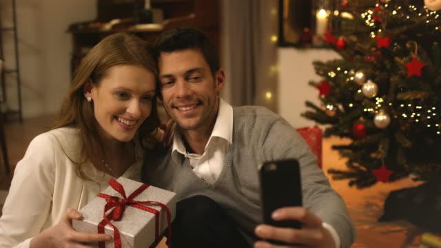 parents taking selfies on christmas eve - christmas gift family bildbanksvideor och videomaterial från bakom kulisserna
