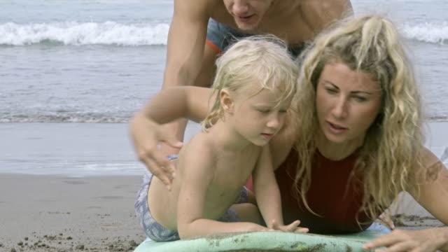 教育の幼い息子を両親にサーフボードに泳ぐ方法 - 息子点の映像素材/bロール