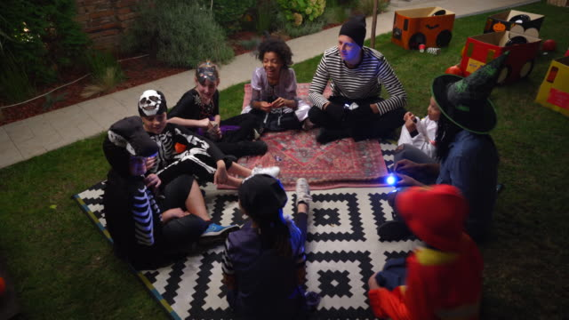 Parents telling scary stories to kids at outdoor Halloween party Parents telling scary stories to kids at outdoor Halloween party halloween covid stock videos & royalty-free footage