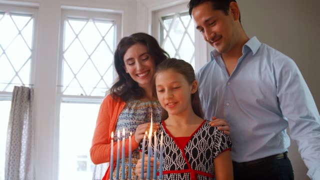 Parents watch daughter light candles in menorah for Shabbat video