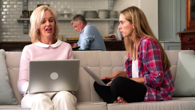 Parents With Adult Daughter Using Laptop Computers At Home video