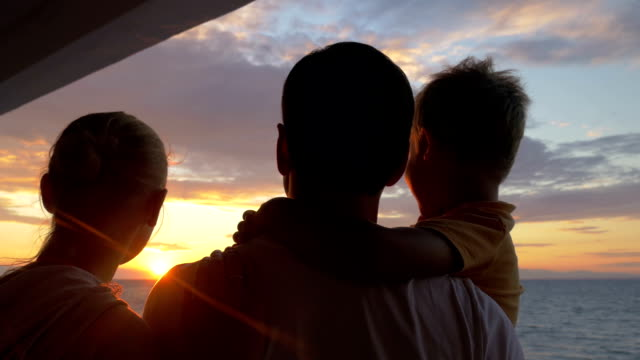 Parents with child looking at sunset and taking selfie