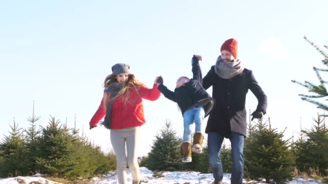 parents with child running in forest - zima filmów i materiałów b-roll
