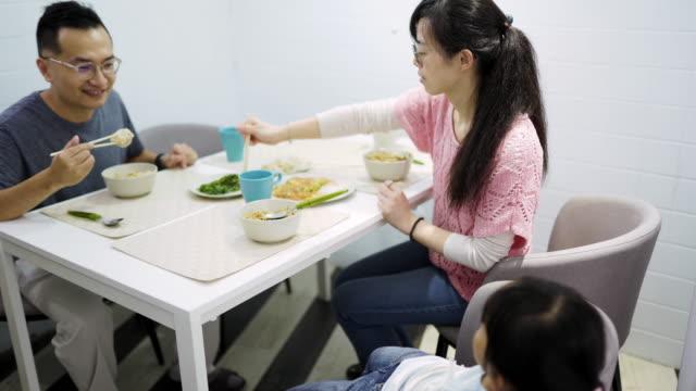vídeos y material grabado en eventos de stock de padres con hija comiendo comida en el comedor - comida china
