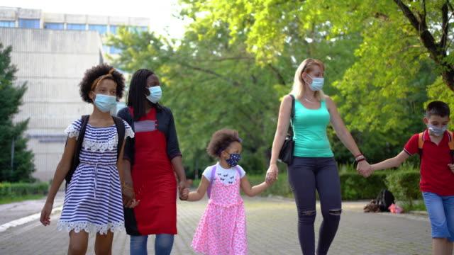 vidéos et rushes de parents avec des élèves d'école primaire allant à l'école avec des masques de visage - enfant masque