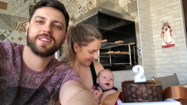 vidéos et rushes de parents avec le fils nouveau-né faisant un chat vidéo à son anniversaire à la maison - photophone
