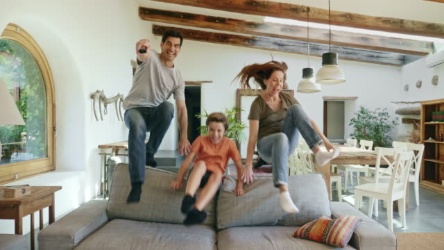 Parents with son jumping over back of sofa to watch tv Slow motion video of energetic Spanish parents in early 40s with son  jumping over sofa with TV remote control. jumping stock videos & royalty-free footage