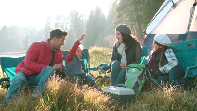 Parents with two kids on a camping trip sitting outside tent video