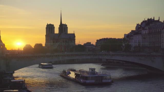 paris, solnedgång på notre dame de paris katedral - turistbåt bildbanksvideor och videomaterial från bakom kulisserna