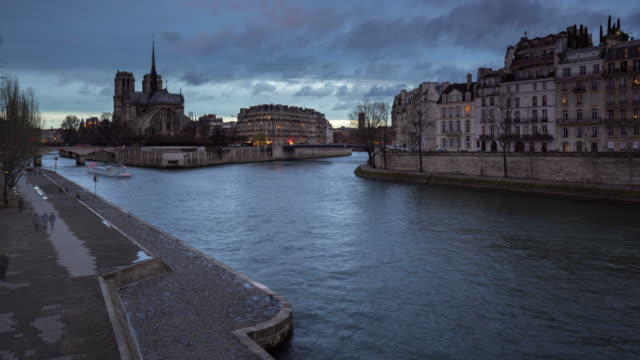 Paris - The Seine River banks by Ile Saint Louis and Ile de la Cite with Notre Dame Cathedral (time-lapse) - vídeo