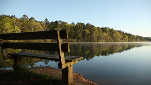 Park Bench Overlooking Beautiful Lake With Reflection At Sunrise