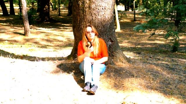 Un parque. La chica está sentada bajo un árbol. Marca el número en el teléfono inteligente. Habla y sonríe. - vídeo