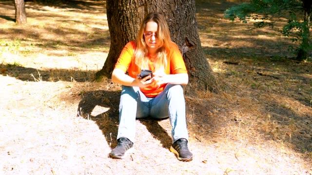 Un parque. La chica está sentada bajo un árbol. Marca el número en el teléfono inteligente. - vídeo