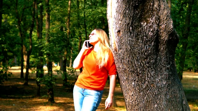Un parque. La chica apoyó sus codos en el tronco del árbol. Habla y sonríe. - vídeo