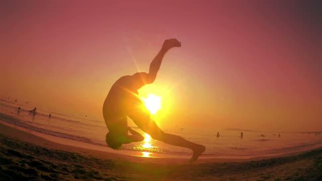 Parkour free runner runs and jumps backflip at summer beach sunset. Steadicam SLOW MOTION shot video