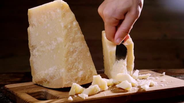 vidéos et rushes de composition de fromage parmesan, sur une planche à découper en bois. une main prend le couteau et brise un couple de pièces à savourer la qualité. - parmesan