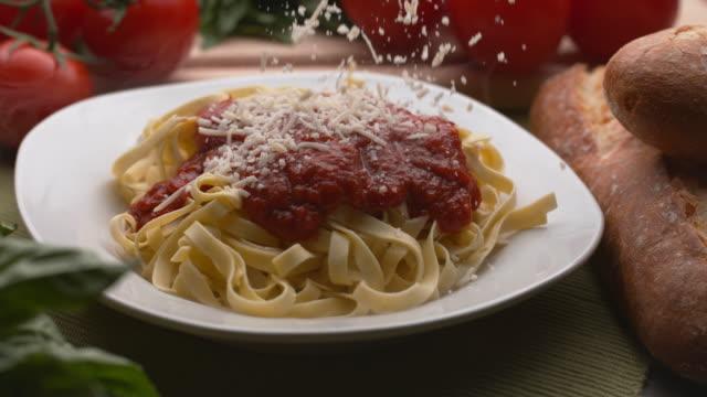 vidéos et rushes de fromage parmesan saupoudré sur pâtes - parmesan
