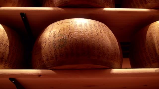 vidéos et rushes de roues de fromage parmesan formes d'épices dans une usine de parmesan - parmesan