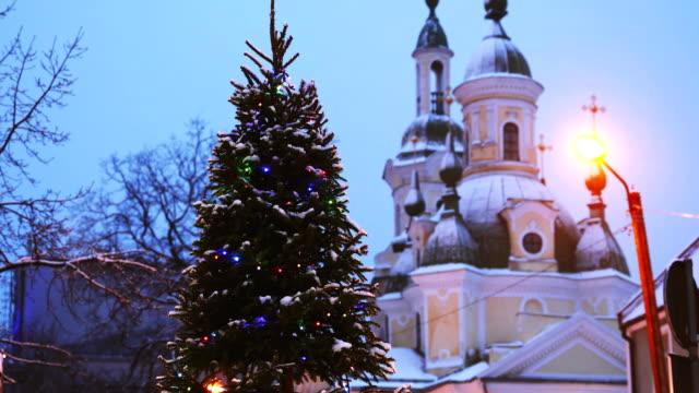 stockvideo's en b-roll-footage met parnu, estland. kerstboom in vakantie nieuwjaar feestelijke verlichting en st. katherine orthodoxe kerk op achtergrond - estland