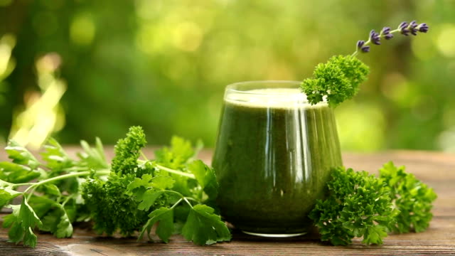 parsley and celery juice in glass on a wooden table video
