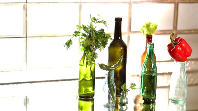 parsley and peppers on a variety of glass bottles - paprica video stock e b–roll