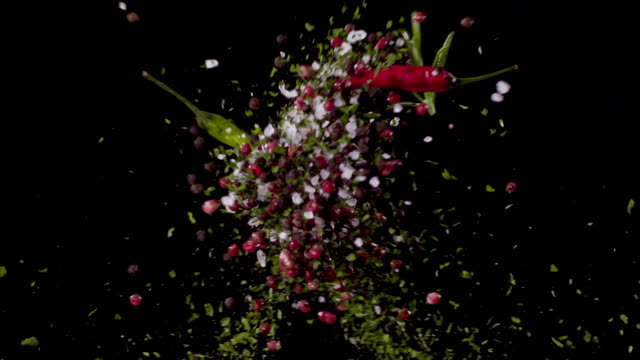 Parsley, Peppercorns, Bay Leaves, Oregano, Sea-Salt, Chili Pepper, Rosemary Colliding in the Air Super Slow Motion Video 1000 fps